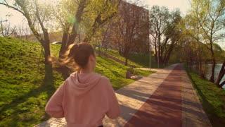 runner wearing sportswear black leggings and pink hoodieback view woman jogging outdoors