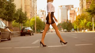 Side view fashionable woman with blond hair wearing white shirt and black skirt and high-heels shoes walking on the road in summer city. slow motion