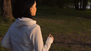 side view young woman running in forest slow motion. caucasian brunette exercising outdoors. fitness athlete wearing white hoodie