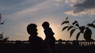 Silhouette father plays with small boy outdoors. Smiling man throwing lovely son up into the air. Happy paternity at sunset in garden