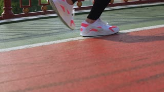 slow motion sport. close up details the woman's legs are shod sneakers white and pink colors. unrecognizable woman running across the bridge