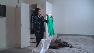 Smiling caucasian brunette returned from the trip unpacking suitcase. Hanging clothes in a wardrobe. young caucasian tourist in apartment