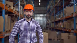 smiling manager near metal racks with boxes wearing casual shirt and orange hard hat. Portrait worker posing in warehouse at work. Happy friendly adult men with beard looking at the camera with smile