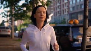 sport and fitness slow motion. portrait happy woman jogging in morning urban city. caucasian athlete running along road with driving cars