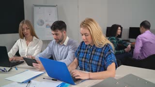 Staff closing laptop and looking at the camera with friendly smile. Young workers in startup company sitting in the modern contemporary office. Casual diverse people using digital device like laptop