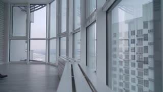 Successful businessman walking in room modern office of home with urban landscape. Guy wearing jacket and looking on the street with high rise building