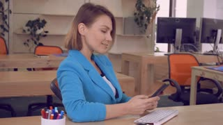successful busineswoman sitting at the working place in the casual modern office using smartphone chatting with children happy smiling. adult woman wearing elegant jacket at work.