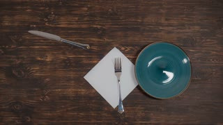 The green plate moves on the table, a knife and fork move next to it, on the table there is a white napkin, a view from the top