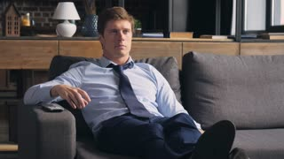 tired man watching tv after hard day. Handsome exhausted businessman relaxing at home