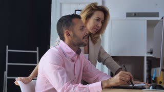 Two designers talking about project. Handsome man drawing using digital tablet near standing caucasian woman looking on display computer with happy smile