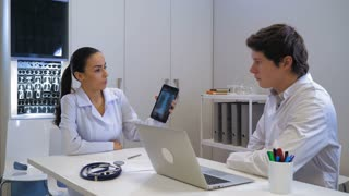 Two doctors discussing x-ray sitting at working place in hospital. Professional woman holding digital tablet with fluorography. Colleagues discuss method of treatment