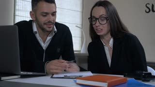 two people discussing project in office, smiling professional workers sitting at the desk looking on paper documents