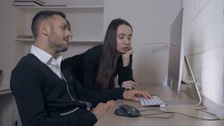 two people looking on display computer discussing some project. attractive caucasian businesswoman standing near working place handsome mixed race businessman