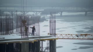 Two workers standing on the end of level construction site. People do some work on the build outdoors in winter season. Man wearing in orange coveralls and hard hat. Urban view on the city with snow