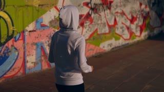 unrecognizable girl jogging in city runner wearing white sport hoodie
