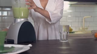 unrecognizable woman pouring green vegetables juice in glass. Female hand holding blender with detox smoothie at home