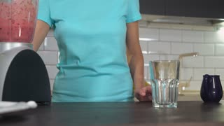 unrecognizable woman pouring red fruit juice in glass. Female hand holding blender with blueberries smoothie in the kitchen. Close up girl amrs with healthy drink