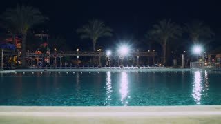 View on the swimming pool in hotel at the evening. Beautiful nature with palm trees and lights. Beach furniture outdoors