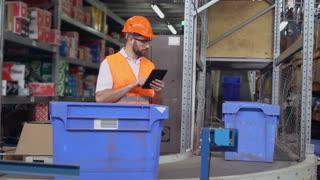 Warehouse worker standing near conveyor with parcels. Manager using digital tablet entering data. Man controls logistic wearing uniform and white shirt