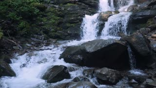 Water from mountain river flow down into pool. slow motion