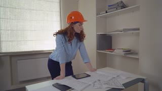 Woman architect standing near desk with blueprint architectural plan. Attractive redhead professional woman looking at the camera with happy smile in office