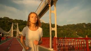 woman has an active leisure. female runner wears white t-shirt.