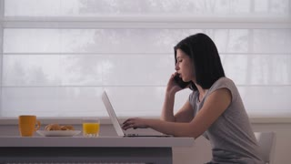 Woman has phone conversation with client check information on computer in the morning. Busy businesswoman has a breakfast working at home