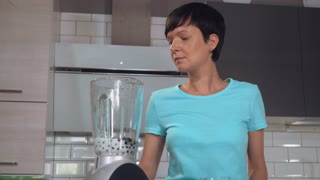 Woman making smoothie with fruits in the kitchen. Young caucasian brunette using blender for preparing healthy juice with berries and milk at home. Healthy drink for better life