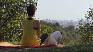Woman resting after workout outdoors. Back view girl wearing sportswear sitting on the grass in park near playing with ball french bulldog. Active leisure at summer season in sunny morning. Beautiful