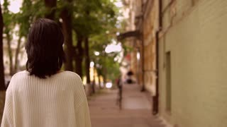 woman walks on the sidewalk. lady is wearing white pullover.