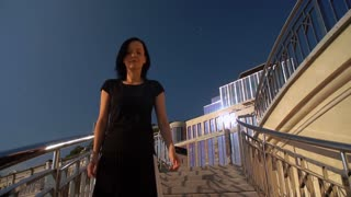 woman wearing black clothes walking against modern architecture background. lady steps down by the balustrade.