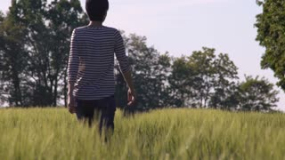 Woman with short haircut walking through the field rear back view. Slow motion. Beautiful nature nature landscape in summer season. Girl wearing casual jeans and striped shirt outdoors