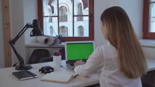 woman working in the office rear back view. . Blonde looking on green screen computer. Lady using pc typing fast