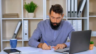 worker writing something on white paper then throws aside the cameras. handsome journalist or writer is in a state of frustration. bearded man unhappy feels fury and frustration
