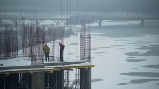 workers walking on the construction site and check. Man wearing in orange coveralls and hard hat. Urban view on the city with snow ice on river and bridge