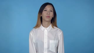 young asian woman dancing funny dance on blue background in studio. attractive millennial girl wearing white casual shirt looking at the camera smiling
