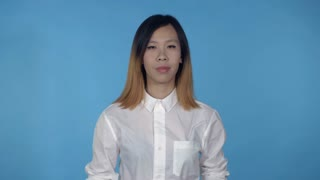 young asian woman posing have fun making faces on blue background in studio. attractive millennial girl wearing white casual shirt looking at the camera smiling