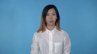 young asian woman posing showing hand gesture loud sound on blue background in studio. attractive millennial girl wearing white casual shirt looking at the camera