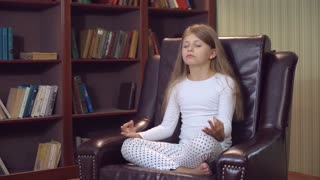 Young baby girl sitting on the big brown leather chair in the lotus position. Kid have fun posing near bookcase in library room at home. Child with long blond hair seven years old wearing white