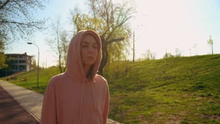 young beautiful woman wearing hood walking on the street after morning running. attractive caucasian girl going after outdoor workout runners run past