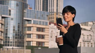 Young brunette scrolling touch screen smartphone outdoors. Happy businesswoman spend coffee break outdoors. Smiling woman standing near office building texting message on smart phone. Caucasian lady