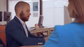 young business man has meeting with unrecognizable woman. bank worker sitting at the workspace using computer talking with client