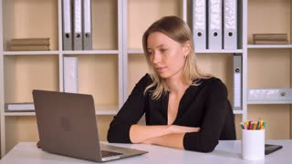 young business woman has online video meeting. worker in start up company using wireless and application for call. smiling employee wearing elegant black dress talking with client looking on screen