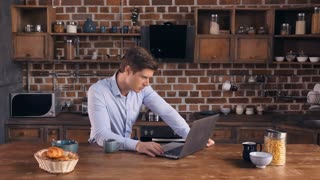 Young businessman at home in the morning. Caucasian man using computer drinking coffee in the kitchen. Guy working in flat reading digital news or documents on laptop