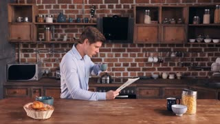 Young businessman drinking coffee reading newspaper in the kitchen at home. Handsome caucasian guy wearing elegant blue shirt reads article in paper magazine morning time in apartment