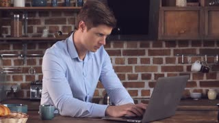 Young businessman have breakfast and working at home. Millennial man sitting in kitchen using laptop typing mail or surfing internet or reading news and drinking coffee in the morning