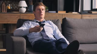 Young businessman in a bad mood at home. Caucasian handsome man resting in flat lying on sofa and watching tv changes channels. Male wearing in elegant clothes and tie