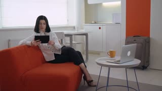 Young businesswoman reading ebook or checking email or surfing internet in hotel room or in apartment with modern white interior. Caucasian woman with black hair using internet on touch screen tablet