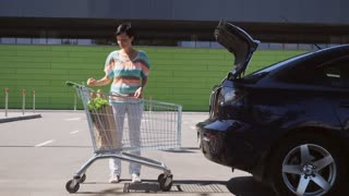 Young caucasian brunette putting bag with groceries and vegetables into car trunk on the parking near store in sunny day. Happy woman after shopping food
