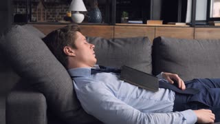 Young caucasian businessman sleeping with book on the sofa in living room. Tired man have a nap after hard day or resting in weekend in flat